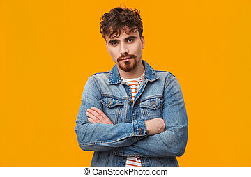 Handsome young bearded man standing isolated over orange