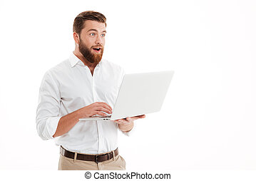 Handsome young bearded man using laptop.