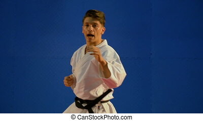 Handsome young black belt karate man exercises punching in...