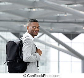 Handsome young black man smiling with bag