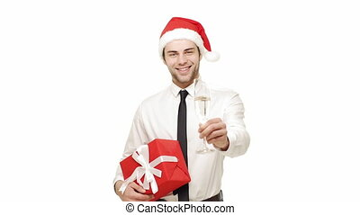 Handsome young blond businessman wearing christmas hat holding glass of champagne smiling laughing with red present.
