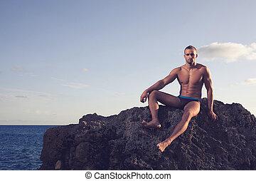Handsome young bodybuilder. sea or