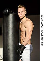 Handsome young boxer shirtless with boxing gloves