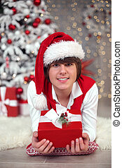 Handsome young boy in santa hat lying by Christmas tree having fun celebrating New year at home. Happy smiling male looking at camera.