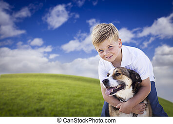 Handsome Young Boy Playing with His Dog in the Grass
