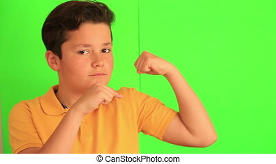 Handsome young boy showing his biceps