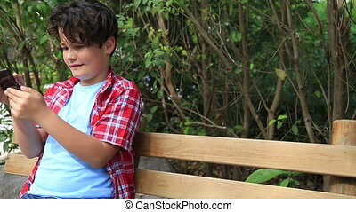Handsome young boy with smartphone - Young boy playing with...
