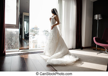 bride in white lacy wedding dress and veil looking through the window
