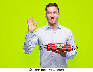Handsome young business man holding an alarm clock bomb doing ok sign with fingers, excellent symbol