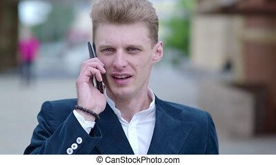 Handsome young business man in a classic suit and coat is talking on smart phone