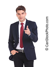 Handsome young business man pointing at the camera.