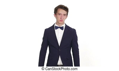 Handsome young business man standing against white background and showing disgust on his face