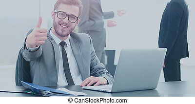 handsome young business man with people in background at office meeting. showing thumbs up
