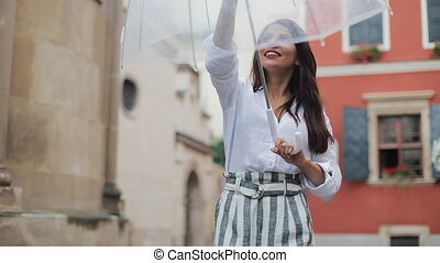 Handsome young business woman looking up the sky and raising hand for checking if the rain stop. She smiling and close her umbrella enjoying the end of the rain