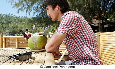 Handsome young businessman in a beach cafe with sea view on palm trees on background and uses mobile phone.