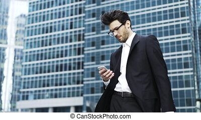 Handsome young businessman in glasses texting outdoors