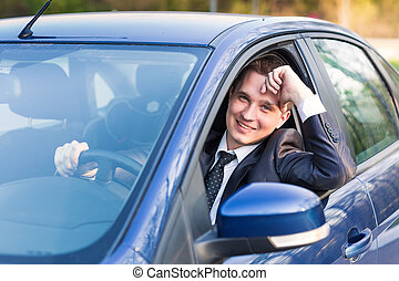 Handsome young businessman in his new car