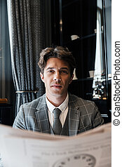 Handsome young businessman in suit reading newspaper