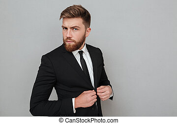 Handsome young businessman in suit standing and looking at camera