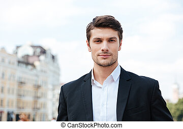 Handsome young businessman in suit standing outdoors