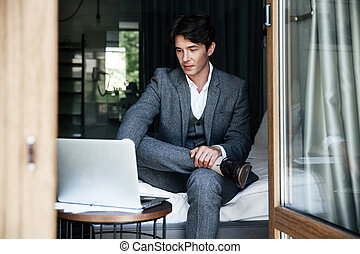 Handsome young businessman in suit working on laptop