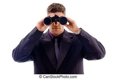 handsome young businessman looking through binoculars