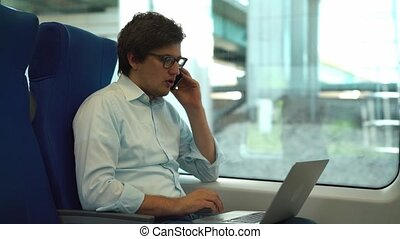 Handsome young businessman on phone and using laptop in a train