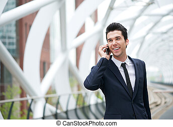 Handsome young businessman on the phone at station