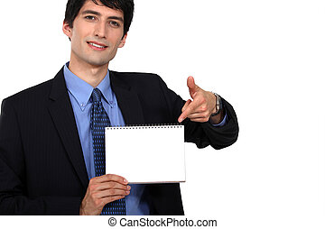 handsome young businessman pointing at spiral notebook