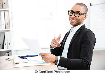 Handsome young businessman pointing finger at camera and holding papers