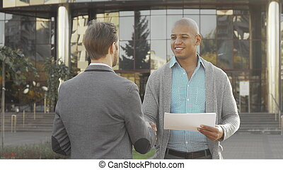 Handsome young businessman shaking hands with his colleague outdoors