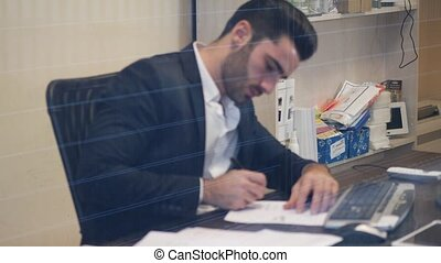 Handsome young businessman sitting at desk in office