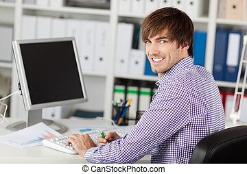Handsome Young Businessman Smiling At Desk
