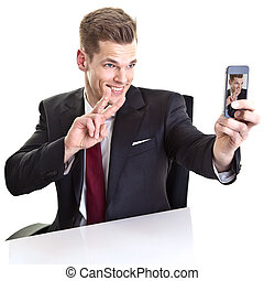 Handsome young businessman taking a selfie with his smartphone