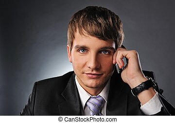 Handsome young businessman talking on mobile phone