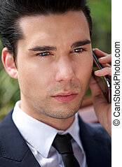 Handsome young businessman talking on phone
