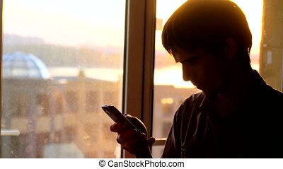 Handsome young businessman talking with smartphone at window on the sunny city view during sunset.