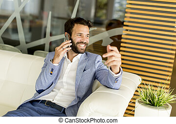 Handsome young businessman using phone in office