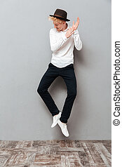 Handsome young caucasian man jumping isolated