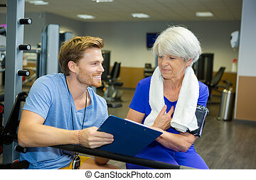handsome young coach working out with an elderly woman