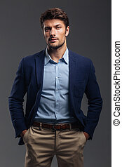 Handsome young confident man standing with hands in pockets