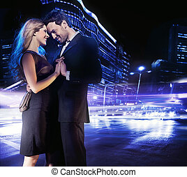 Handsome young couple dancing on the street and smiling
