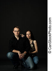 handsome young couple posing sitting in studio