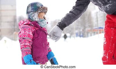 Handsome young dad and his little cute daughter are having fun outdoor in winter. Enjoying spending time together while making snow angels. Family concept