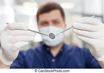 Handsome young dental doctor is preparing for work