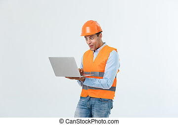 Handsome young engineer man over grey wearing safety helmet with shocked surprise face.