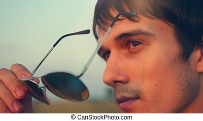 Handsome young fashion man wearing sunglasses and looks sunset in the field
