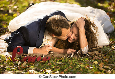 young groom kissing beautiful bride in cheek lying on grass at p