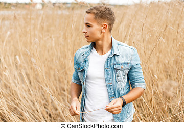 1206654a Handsome young guy in jeans clothes and a white T-shirt is walking outdoors  in