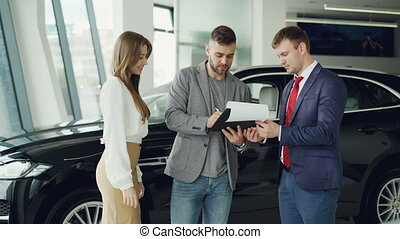 Handsome young guy is signing sale and purchase agreement in car dealership, getting key fob from salesman and giving it to his wife, she is smiling and kissing him.
